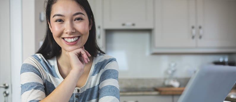 An Asian woman is sitting in front of her laptop and smiling, possibly after registering for one of CanScribe's online programs