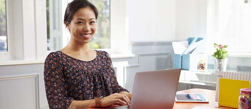 A younger Asian woman is smiling while working on her laptop, perhaps because she was just received financial assistance to train with CanScribe