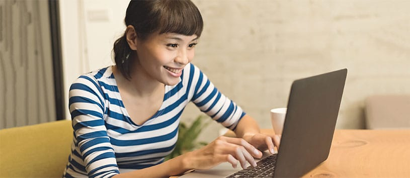 A cute Asian woman with bangs is smiling as she works on her laptop while working on the Medical Terminology program