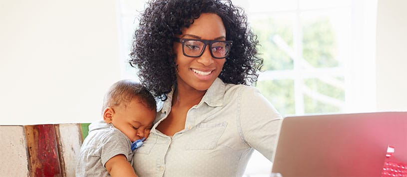 A woman who may have trained at CanScribe Career College is looking at a laptop screen while holding her infant