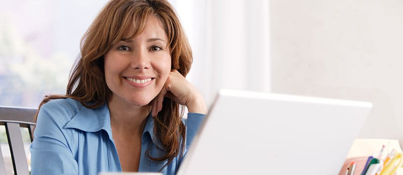 A proud-looking woman is sitting in front of her laptop and smiling for the camera, possibly after reading CanScribe employer testimonials